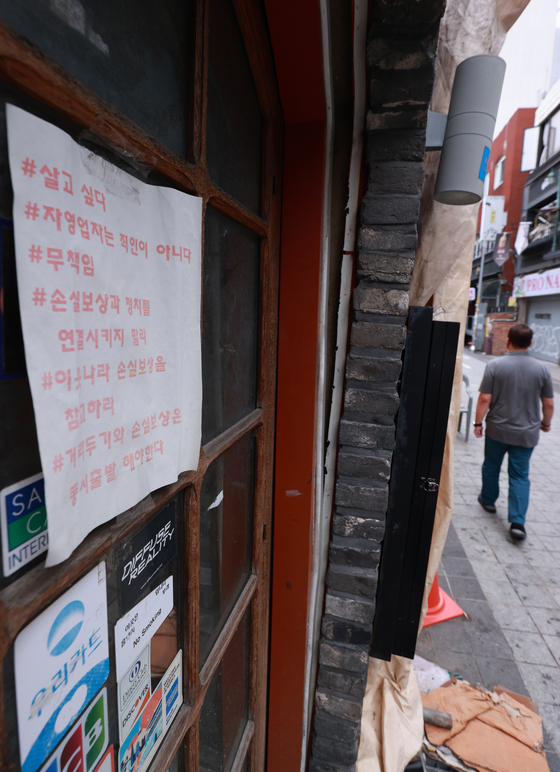A sign condemning the government's Covid-19 social distancing measures is on display at the front of a restaurant in Itaewon, central Seoul, on Monday. According to an emergency committee of self-employed business owners, a drive-through protest that calls for eased social distancing restrictions is scheduled in nine cities on Wednesday night. [YONHAP]