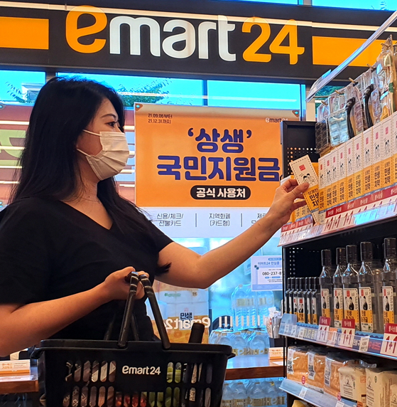 A model shops at an Emart24 store, where a sign that promotes stimulus check spending is hung. [EMART24]
