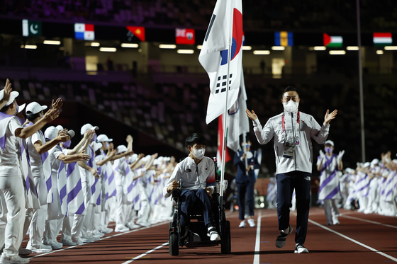 Jeong Ho-won carries the Korean flag during the closing ceremony of the 2020 Tokyo Paralympics on Sunday. [REUTERS/YONHAP]