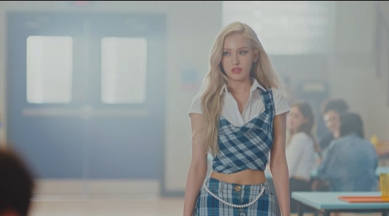 """Singer Jeon Somi wears a plaid crop top and skirt in her music video for """"Dumb Dumb"""" (2021), set in an American-style high school. [THE BLACK LABEL]"""