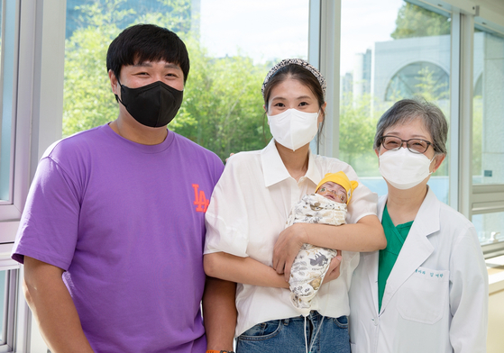 Asan Medical Center's Prof. Kim Ellen Ai-rhan, far right, and the parents of baby Gun-woo pose for a picture at the medical center in southern Seoul on Monday. Gun-woo, the smallest premature baby to survive in Korea, was discharged from the hospital after five months of intensive care. [ASAN MEDICAL CENTER]