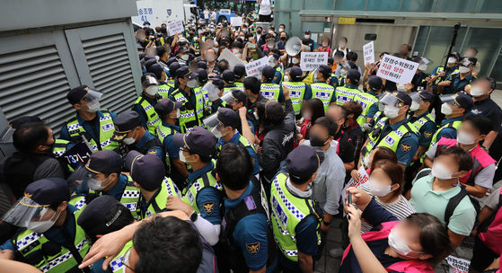 Members of the Korean Confederation of Trade Unions (KCTU) confront policemen in front of the Jongno Police Precinct in central Seoul on Monday, demanding the release of KCTU Chairman Yang Kyeung-soo who is scheduled to be handed over to the prosecution on Monday, on a charge of organizing illegal massive rallies. [NEWS1]