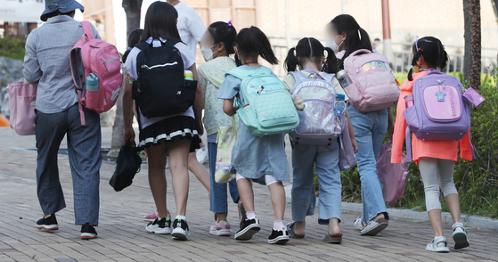 Students arrive at an elementary school in Seodaemun District, western Seoul on Monday, as more students were allowed to return to their classrooms. [NEWS1]