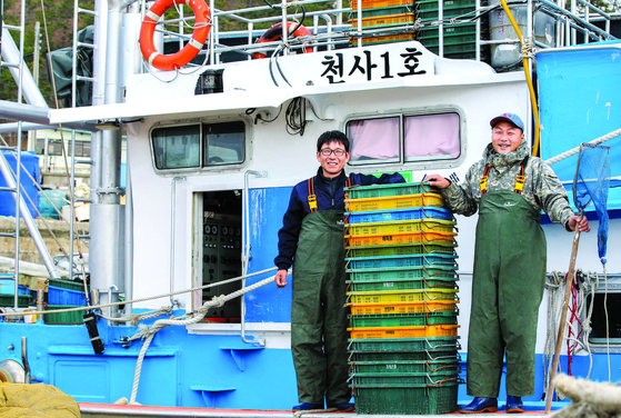 Two young fishermen pose on a fishing vessel they rented cheaply from the Shinan County, South Jeolla, in December 2019. [JANG JEONG-PIL]