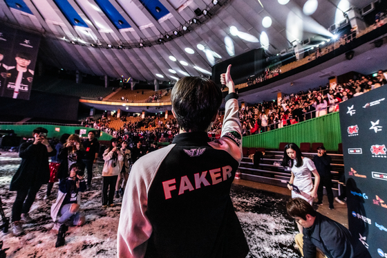 Lee ″Faker″ Sang-hyeok holds his thumb up toward the crowd after winning the 2019 LCK Spring Split Finals. Lee Se-hyun asked Faker to take this pose. The shot was shared around the world and was later used in a subway station birthday ad for Faker. [RIOT GAMES]