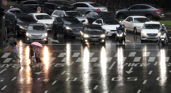 Passenger cars, with their headlights turned on, wait at a traffic light near Seoul City Hall on Tuesday as it gets dark early, owing to rain clouds. [YONHAP]