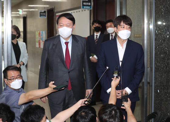 Former Prosecutor General Yoon Seok-youl, the leading ruling party presidential candidate, left, and People Power Party head Lee Jun-seok speak to reporters after a one-on-one meeting Monday at the National Assembly in western Seoul. [YONHAP]