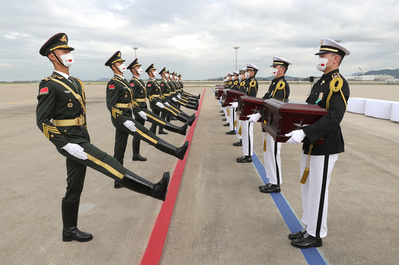 South Korean and Chinese soldiers take part in a handover ceremony at Incheon International Airport Thursday to repatriate the remains of 109 Chinese troops killed during the 1950-53 Korean War. The remains were excavated from battle sites from the war between 2019 and 2020, including at the Arrowhead Ridge in the demilitarized zone. [DEFENSE MINISTRY]