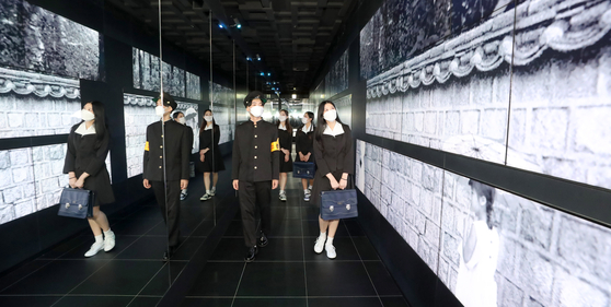 Models dressed in 1960s-style school uniforms walk past black-and-white photo images displayed at Lotte Tower's observatory Seoul Sky in Jamsil, Seoul, on Tuesday. Lotte World is exhibiting works by late photographer Han Young-so of 1960s Seoul. Han was known as one of the leading photographers in fashion and advertisement. [YONHAP]