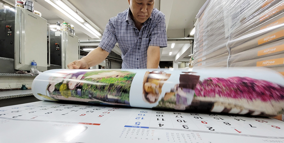 An employee checks next year's calendar at a printing press in Jung District in Seoul on Tuesday. Korea has a busy year in 2022 starting with the presidential election on March 9 and local elections to be held on June 1. While traditional calendars have seen a sharp drop in sales due to smartphones, they still remain popular for nostalgic and sentimental reasons. [YONHAP]
