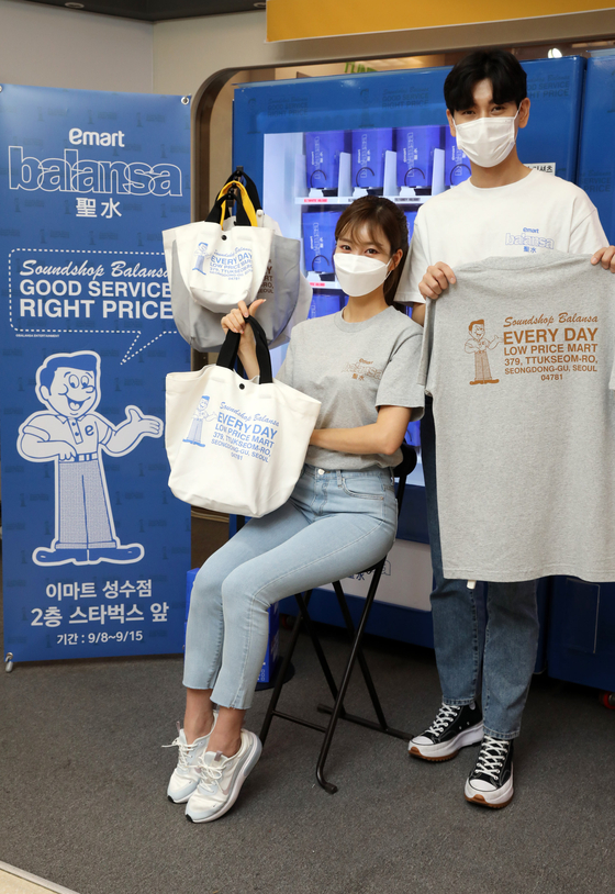 Models hold a T-shirt and a canvas bag released Wednesday by Emart in collaboration with apparel company Balansa. The clothes will be sold online on SSG.com and via a vending machine located in Emart's Seongsu branch in eastern Seoul through Sept. 15. [EMART]
