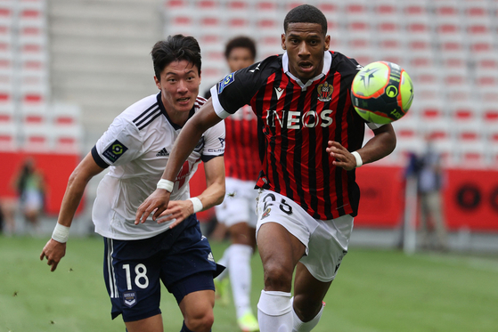 Bordeaux's Korean forward Hwang Ui-jo challenges Nice's French defender Jean-Clair Todibo during the French L1 Huisclos football match between O.G.C Nice and F.C des Girondins de Bordeaux at Allianz Riviera stadium in Nice, southeastern France, on August 28, 2021. [AFP/YONHAP]