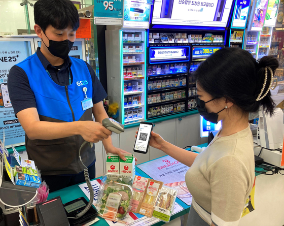 A model picks up products she bought from the Danggeun Market app at a GS25 store. [GS RETAIL]