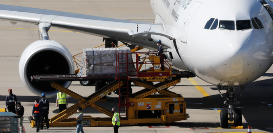 Workers move boxes carrying some 976,500 doses of Pfizer and Moderna vaccines from a chartered plane at Incheon International Airport on Wednesday. This is the second batch of some 1.5 million doses Romania has agreed to provide Korea in exchange for vaccines and other medical supplies. [YONHAP]