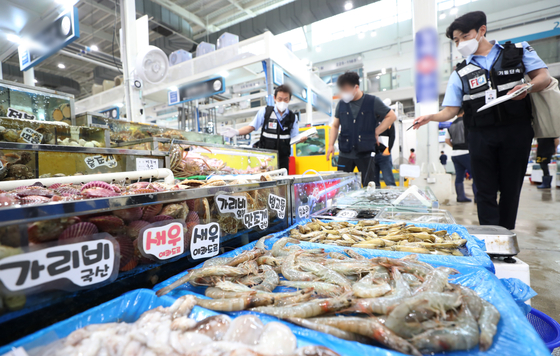 Officials from the National Fishery Products Quality Management Service under the Ministry of Oceans and Fisheries inspect the markings of where the seafood items came from at the Suwon Fish Market on Thursday. Many people are expected to head to the market in the next couple of days to buy foods for Chuseok, the Korean harvest holidays. [NEWS1]