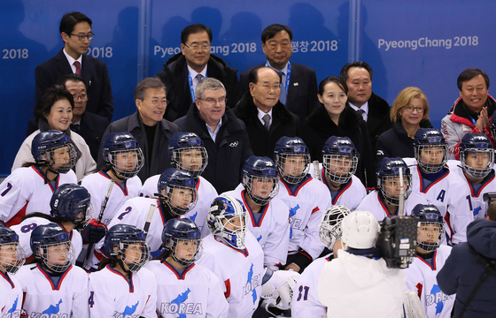 International Olympic Committee (IOC) President Thomas Bach, President Moon Jae-in, Kim Yo-jong, the North Korean leader's younger sister, and other officials from Seoul and Pyongyang pose with the inter-Korean women's ice hockey at the PyeongChang Winter Olympics in February 2018. [YONHAP]