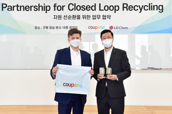 Hur Sung-woo, right, executive vice president of LG Chem's petrochemical global business development team, and Ryan Brown, left, vice president of environment health & safety at Coupang, pose for a photo with plastic pellets and bags that have been produced from plastic waste after signing an agreement Thursday. [LG CHEM]