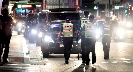 Police forces are dispatched at Yanghwa Bridge in Seoul on Wednesday night as a group of self-employed workers stage rolling rallies in nine cities to urge the government to lift Covid-19 restrictions on their businesses which have been hurt by the implementation of the highest level of social distancing against the spread of the coronavirus. [YONHAP]