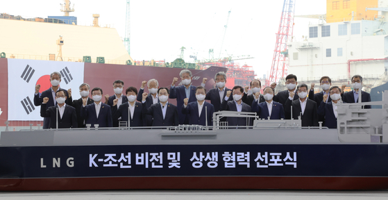 """President Moon Jae-in, front row center, poses with industry and government officials during the """"K-ship"""" ceremony held at Samsung Hyundai Heavy shipyard in Geoje, South Gyeongsang, on Thursday. The attendees include: from first row right, Lee Sung-geun, Daewoo Shipbuilding and Marine Engineering CEO; Ka Sam-hyun, Korea Shipbuilding & Offshore Engineering CEO; Finance Minister Hong Nam-ki; Jung Jin-taek, Samsung Heavy Industries CEO; President Moon and Industry Minister Moon Sung-wook.[YONHAP]"""