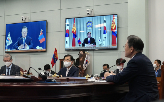 President Moon Jae-in, right, holds a virtual summit with Mongolian President Ukhnaagiin Khurelsukh at the Blue House in central Seoul on Friday as the two countries upgraded bilateral relations to a strategic partnership. [JOINT PRESS CORPS]