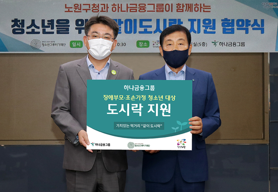 Kim Jung-tai, chairman of Hana Financial Group and the group's Stump Foundation for Youth, right, pose for a photo with Nowon District Mayor Oh Seung-rok after inking a partnership on Monday to cooperate on a social responsibility project to give out lunchboxes to teenagers living with a parent with a disability or those raised by their grandparents. [HANA FINANCIAL GROUP]