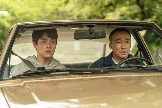 Joon-kyung's father Tae-yoon (played by actor Lee Sung-min), the driver who operates the very train that always passes the village, scoffs at the idea of building a train station in his village. [LOTTE ENTERTAINMENT]