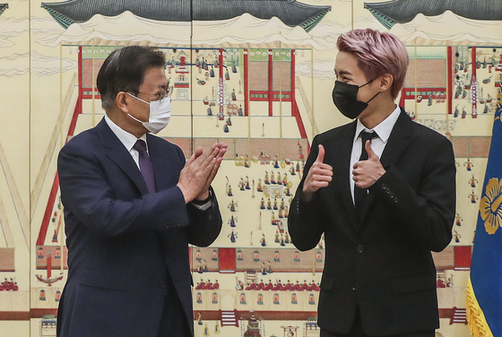 BTS member J-Hope, right, gives President Moon Jae-in a thumbs up at a ceremony appointing the K-pop boy band as special presidential envoys attended by senior Blue House officials and Big Hit Music and HYBE executives Tuesday. [JOINT PRESS CORPS]
