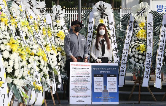 Surrounded by standing wreaths that were sent by dozens of frustrated couples across the nation, a couple holds a sign demanding the easing of government social distancing restrictions on weddings at a protest sponsored by the Federation of Korean Newlyweds Thursday morning. [NEWS1]