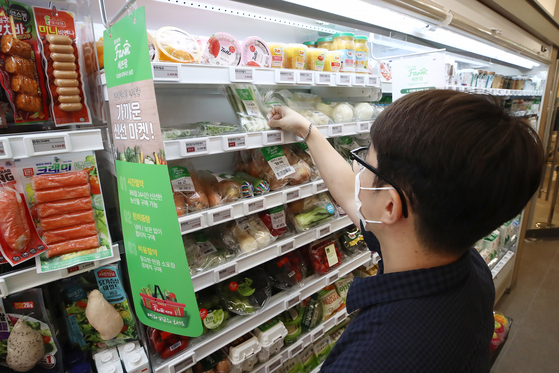 A customer shops at a 7-Eleven in Seoul on Tuesday. Thanks to the government's emergency relief grant, sales of meat and fruit have increased. According to 7-Eleven, sales of meat products between Sept. 7 and Sept. 12 surged 176.2 percent while fruit sales jumped 94.4 percent compared to the previous week. GS25 also saw meat product sales surge 297.7 percent during the same period. [YONHAP]