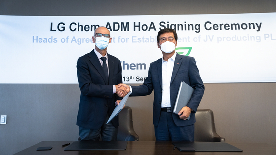 LG Chem CEO Shin Hak-cheol, right, shakes hands with Juan Luciano, CEO of Archer Daniels Midland, after signing an agreement at the U.S.-based company's headquarters in Chicago on Monday to build a poly lactic acid plant. [LG CHEM]