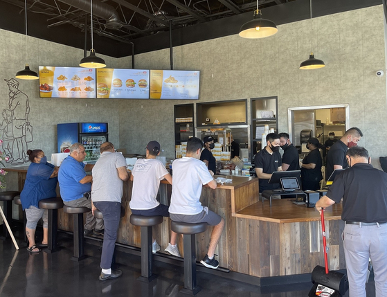 People eat Mom's Touch chicken sandwiches at its first official U.S. store in Los Angeles. [MOM'S TOUCH]