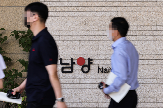 Namyang Dairy Products shareholders leave the building following an extraordinary shareholders' meeting held at the company headquarters in Gangnam, southern Seoul, on Tuesday. [YONHAP]
