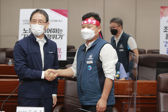 Members from Seoul Metro and the Seoul Transit Corporation Labor Union shake hands after reaching a last-minute agreement at the Seoul Metro Headquarters in Seongdong District, eastern Seoul, shortly before midnight on Monday. Accordingly, a strike by Seoul subway workers scheduled for Tuesday was called off. [NEWS1]