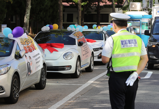Members of the Federation of Korean Newlyweds hold a wedding car protest at the public parking lot of Yeouido Park, western Seoul, on Wednesday. Claiming that newlyweds experienced significant financial losses due to the constantly changing social distancing regulations to curb the Covid-19 spread, the betrothed couples in the federation demanded the easing of the government's restrictions on weddings. [YONHAP]