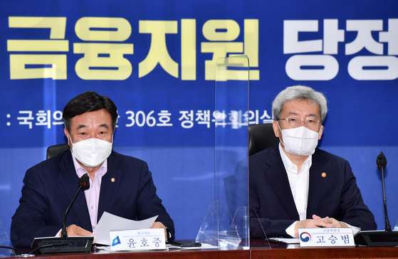 Democratic Party floor leader Yun Ho-jung, left, and FSC Chairman Koh Seung-beom speak during a meeting at the National Assembly on Wednesday. The DP and the government agreed to extend the debt suspension program for another six month. [YONHAP]