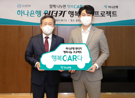 Park Sung-ho, left, CEO of Hana Bank, and Song Min-pyo, CEO of Coactus, pose after attending a ceremony celebrating the bank's donation of two liquified petroleum gas-powered vehicles in Hana's headquarters in Jung District, central Seoul, on Wednesday. [HANA BANK]