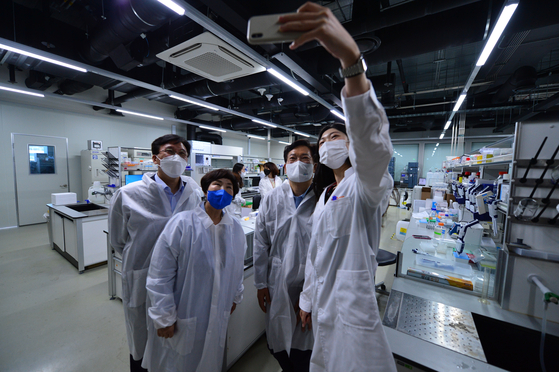Song Young-gil, head of the ruling Democratic Party, second from right, poses with researchers at SK Bioscience's R&D center in Seongnam, Gyeonggi to show support for their study into Covid-19 vaccines. [YONHAP]