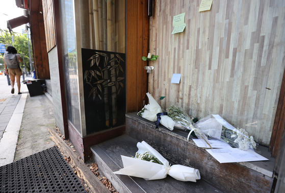 Flowers and hand-written notes are left to mourn the 57-year-old restaurant owner who was found dead Sept. 7. [YONHAP]