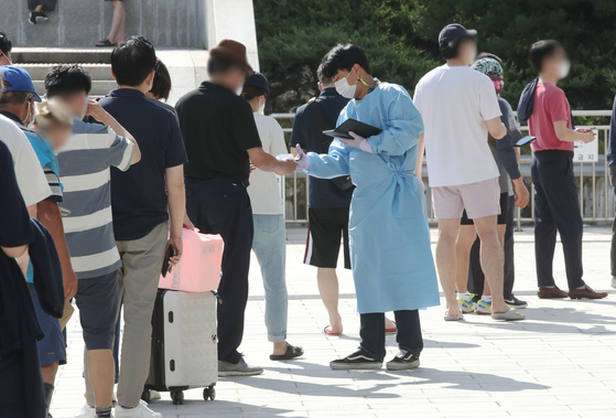 People stand in line to get Covid-19 tests at a screening station at Suseo Station in southern Seoul on Wednesday, the last day of the Chuseok holiday. [YONHAP]