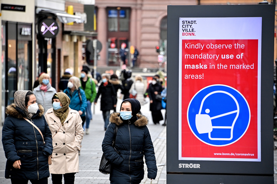 Pedestrians walk past a sign indicating that masks are mandatory in the marked areas in Bonn, Germany, March 13. In Germany, many stores that had been closed for months have opened again. [EPA/YONHAP]