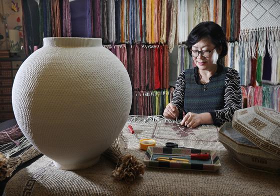 Hong Yeun-hwa, a master of jiseung, a type of paper craft, is making a moon jar at a studio in Seongnam, Gyeonggi. [PARK SANG-MOON]