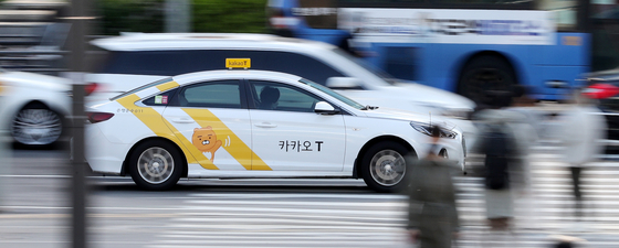 A taxi registered with Kakao T, a mobility affiliate of Kakao, drives on the road in central Seoul. [NEWS1]