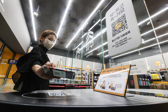 An Emart24 employee checks into an unmanned convenience store in Coex, southern Seoul, using a QR code on Thursday. Customers can enter the store after receiving a QR code when they register a credit or debit card. They can pick up products and leave the store without scanning their purchases, with payments processed automatically. [YONHAP]