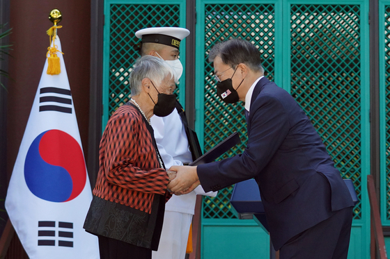 President Moon Jae-in, right, presents posthumously an Order of Merit for National Foundation to the late Kim No-di for her contributions to the Korean independence movement against Japan, accepted by her descendent at a ceremony held at the Korean Language Flagship Center at the University of Hawaii at Manoa Wednesday. [YONHAP]
