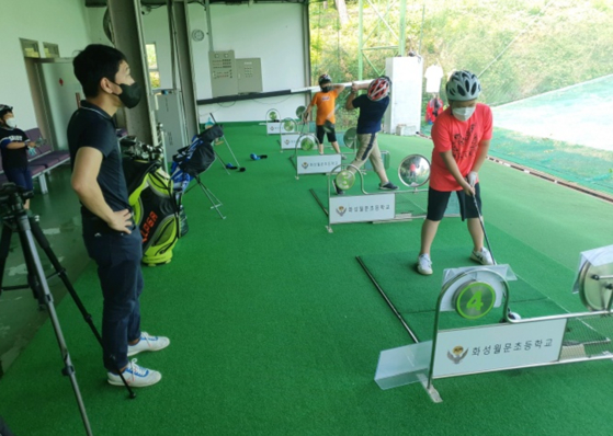 Students at Hwaseong Wolmun Elementary School in Hwaseong, Gyeonggi, are learning golf during gym class. The school established its own golf facilities in order to differentiate itself from other schools in the region and attract more students. The school's golf program has helped Hwaseong Wolmun Elementary School to stay open amid a declining number of students in Hwaseong city due to the aging society. [HWASEONG WOLMUN ELEMENTARY SCHOOL]