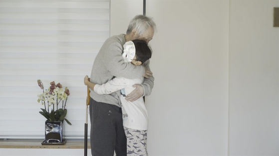 """Kim Tschang-yeul hugs his grandson in """"The Man Who Paints Water Drops."""" [MIRU PICTURES]"""