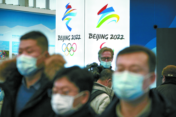 People wear face masks to protect against Covid-19 look at an exhibit at a visitors center at Winter Olympic venues in Yanqing on the outskirts of Beijing. Beijing Olympic organizers showed off the downhill skiing venue and the world's longest bobsled and luge track last Friday, one year ahead of the opening of the 2022 Winter Games. [AP/YONHAP]