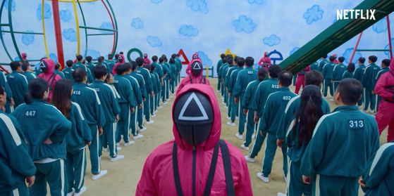 """A scene from """"Squid Game"""" shows the survival game players in green track suits. [NETFLIX]"""
