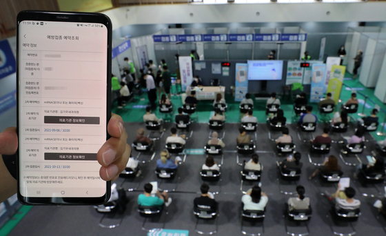 Patients wait for any adverse reactions after their vaccinations at a local gym in Seodaemun District, western Seoul, on Tuesday afternoon. The screen of the mobile phone being held up shows the vaccination registration information of an unidentified person. [NEWS1]