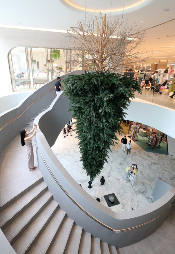 """An """"upcycled"""" tree on display at Lotte Department Store's branch in Dongtan, Gyeonggi. According to Lotte Department Store, the tree is artwork by artist Im Jung-joo. It is part of a series titled """"Noneloquent."""" Some 100 artworks are on display, including a painting by British artist David Hockney titled """"In the Studio, December 2017,"""" to attract customers. The Dongtan branch, which opened last month, is the first new Lotte branch in seven years. [LOTTE SHOPPING]"""